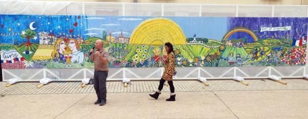 Une fresque géante et colorée va embellir l'esplanade de la Halle ronde givrotine pendant le mois d'octobre